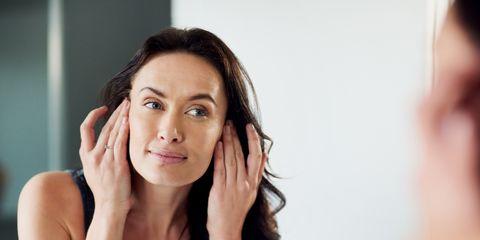 mujer observando su piel frente al espejo