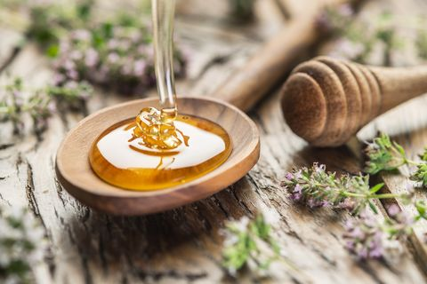herbal honey pouring into the wooden spoon