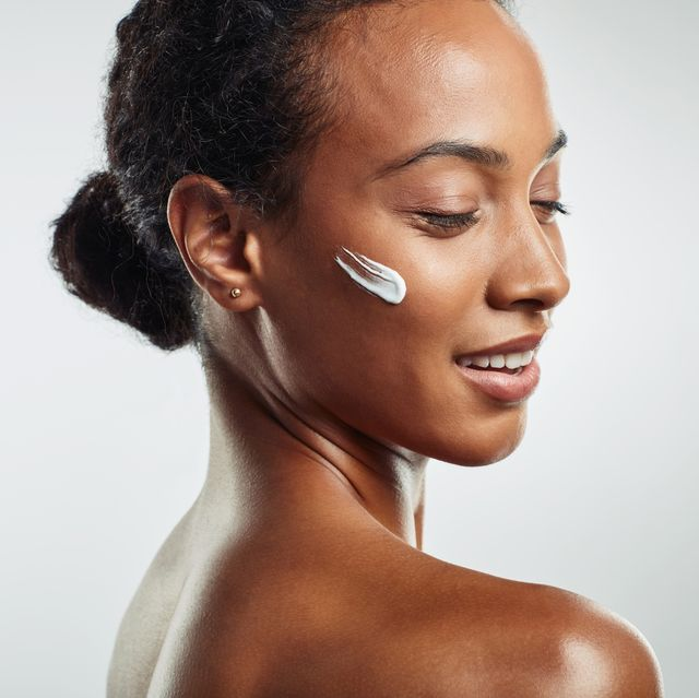 black woman with beautiful skin, eyes closed, with streak of face mask product on cheek