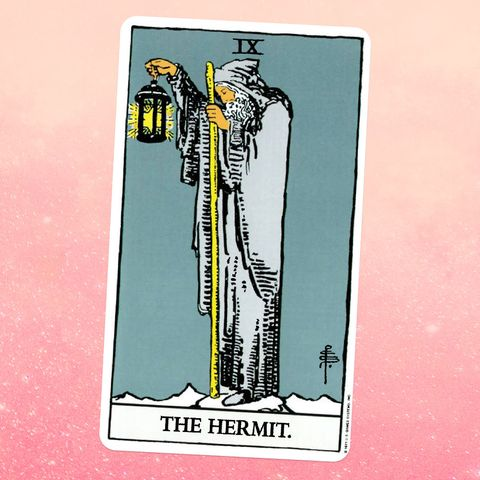 the tarot card the hermit, showing an old man in a beard and a gray robe holding a wooden staff and a lantern