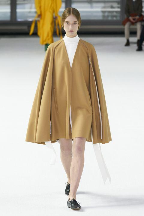 Fashion show, Fashion model, Fashion, Runway, Clothing, Yellow, Outerwear, Fashion design, Haute couture, Overcoat,