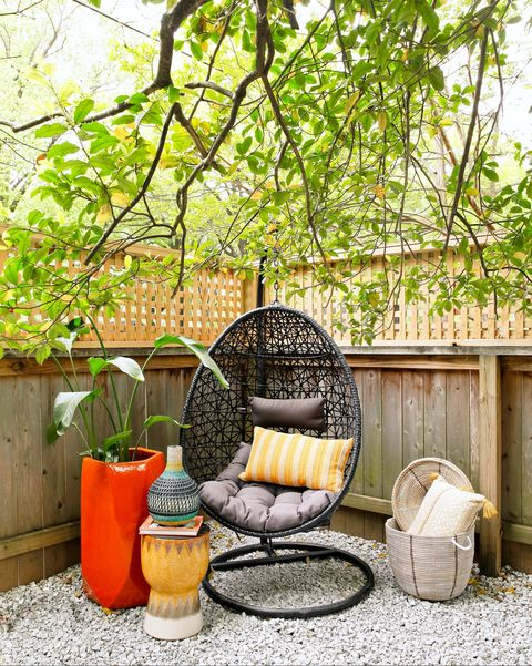hanging black seat with yellow stool and big red planter next to it