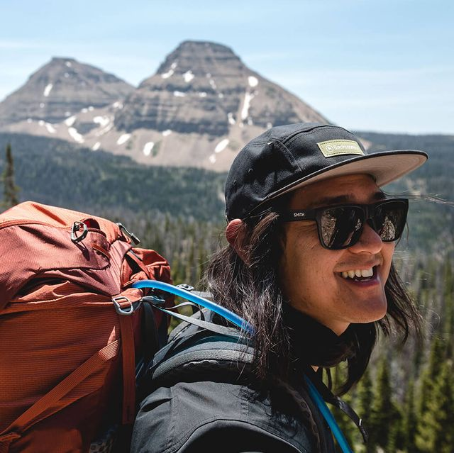 person smiling wearing backcountry gear in front of mountain
