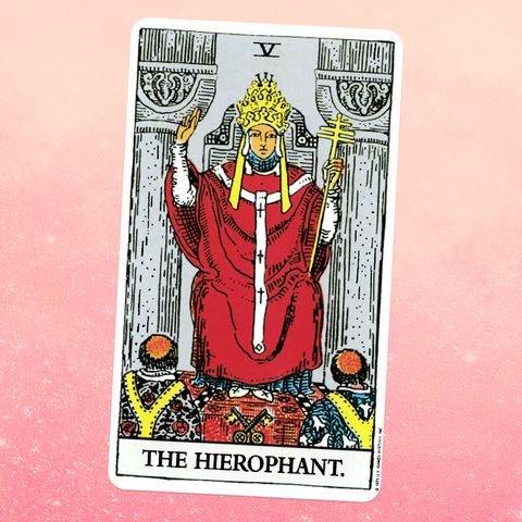 the tarot card the hierophant, showing a person in a red robe and gold crown sits on a throne, with two people kneeling in front of them