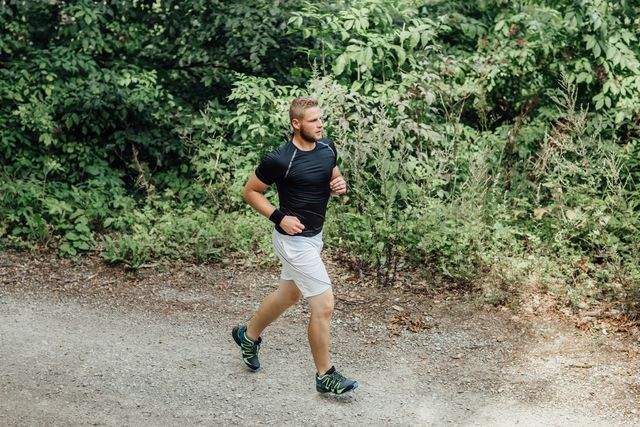 high angle side view of male runner running along a nature trail