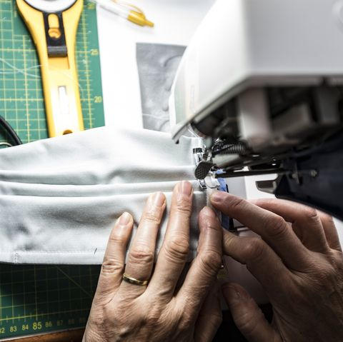 high angle view close up of mature woman sewing protective face masks during coronavirus pandemic