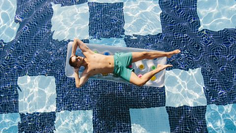 High angle view of a young man in sunglasses sunbathing in swimming pool on inflatable pool raft