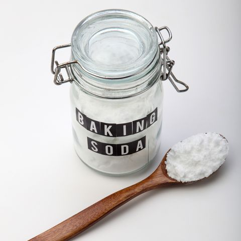 high angle view of baking soda in jar and wooden spoon over white background