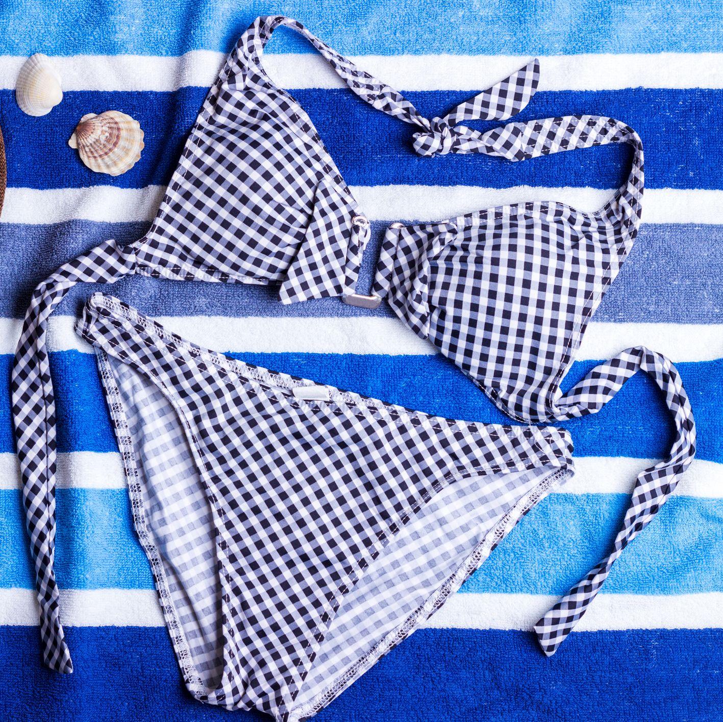 High Angle View Of Bikini With Hat And Seashells On Beach Towel