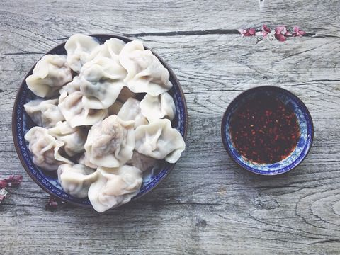 Chinese Dumpling And Chili Oil Served In Bowls On Wooden Table