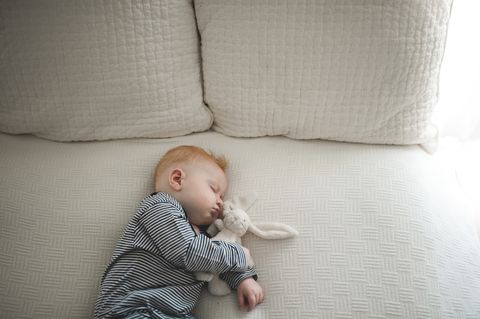 High angle view of cute baby boy sleeping with stuffed toy on bed