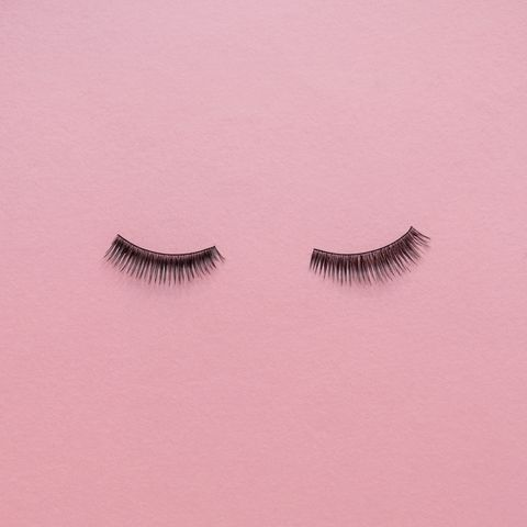 high angle view of false eyelashes on pink table