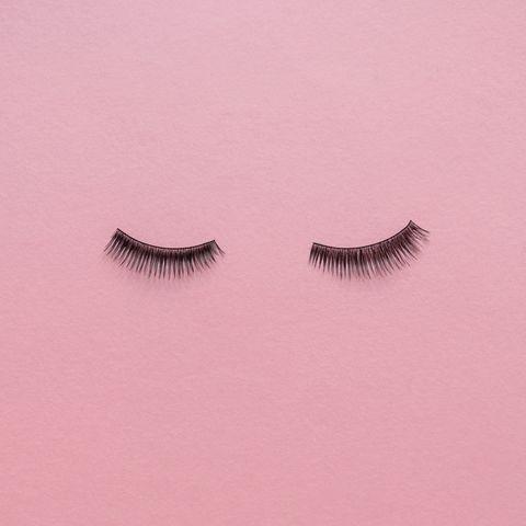 high angle view of false eyelashes on pink table