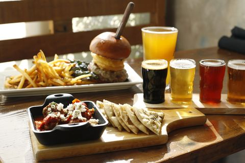 High angle view of fast food with beer served on wooden table in restaurant
