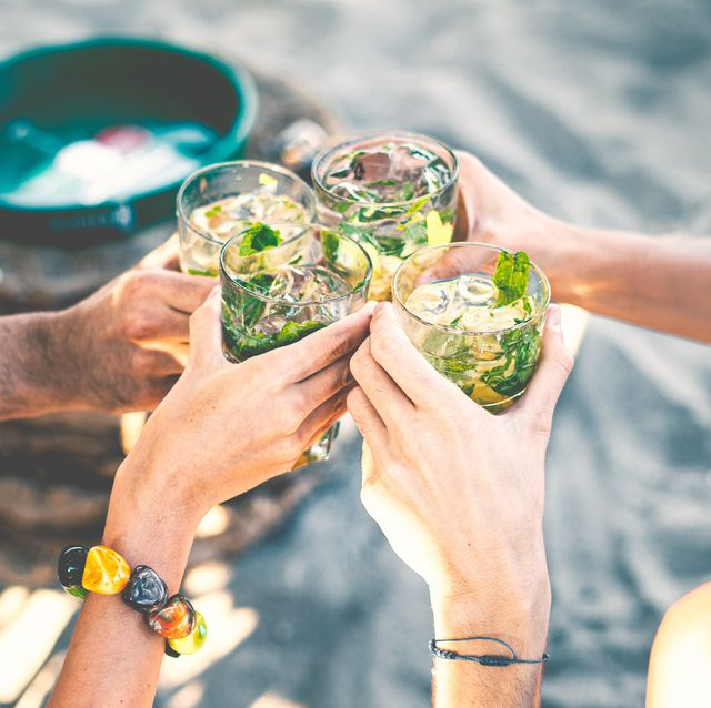 high angle view of group of people toasting holding glass with tropical  cocktails