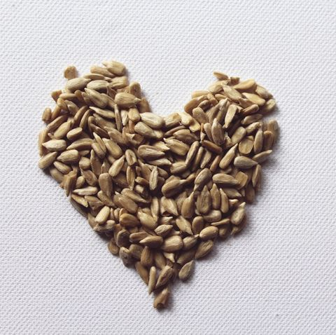 high angle view of heart shape made of sunflower seeds on white table