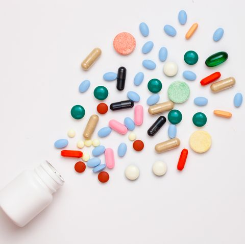 High Angle View Of Multi Colored Pills And Bottle Against White Background