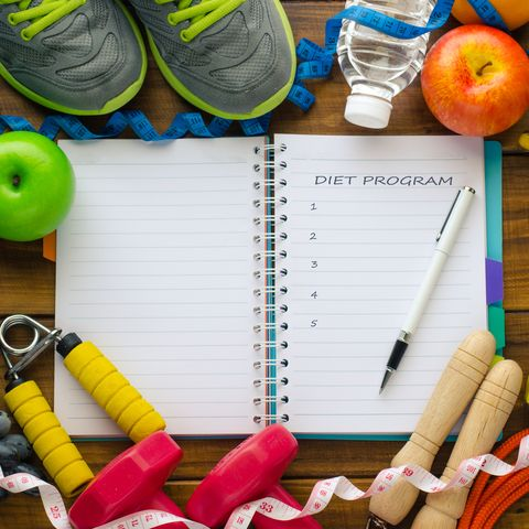 high angle view of open book amidst fruits and exercise equipment on table
