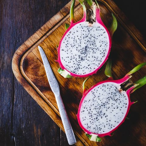 high angle view of pitaya with knife and cutting board on wooden table