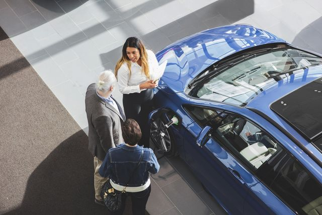 high angle view of saleswoman showing car to customers at showroom