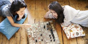 High angle view of sisters playing chess at home