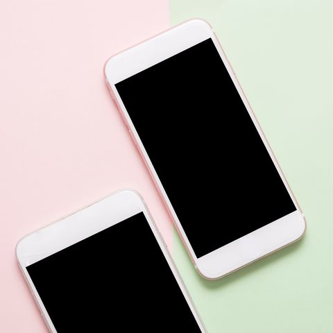 High Angle View Of Smart Phones On Colored Background