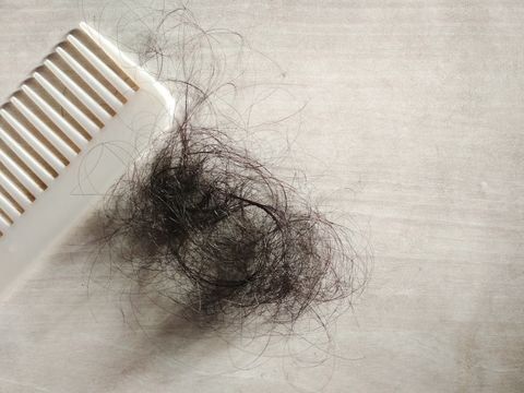 high angle view of tangled hair by comb on table