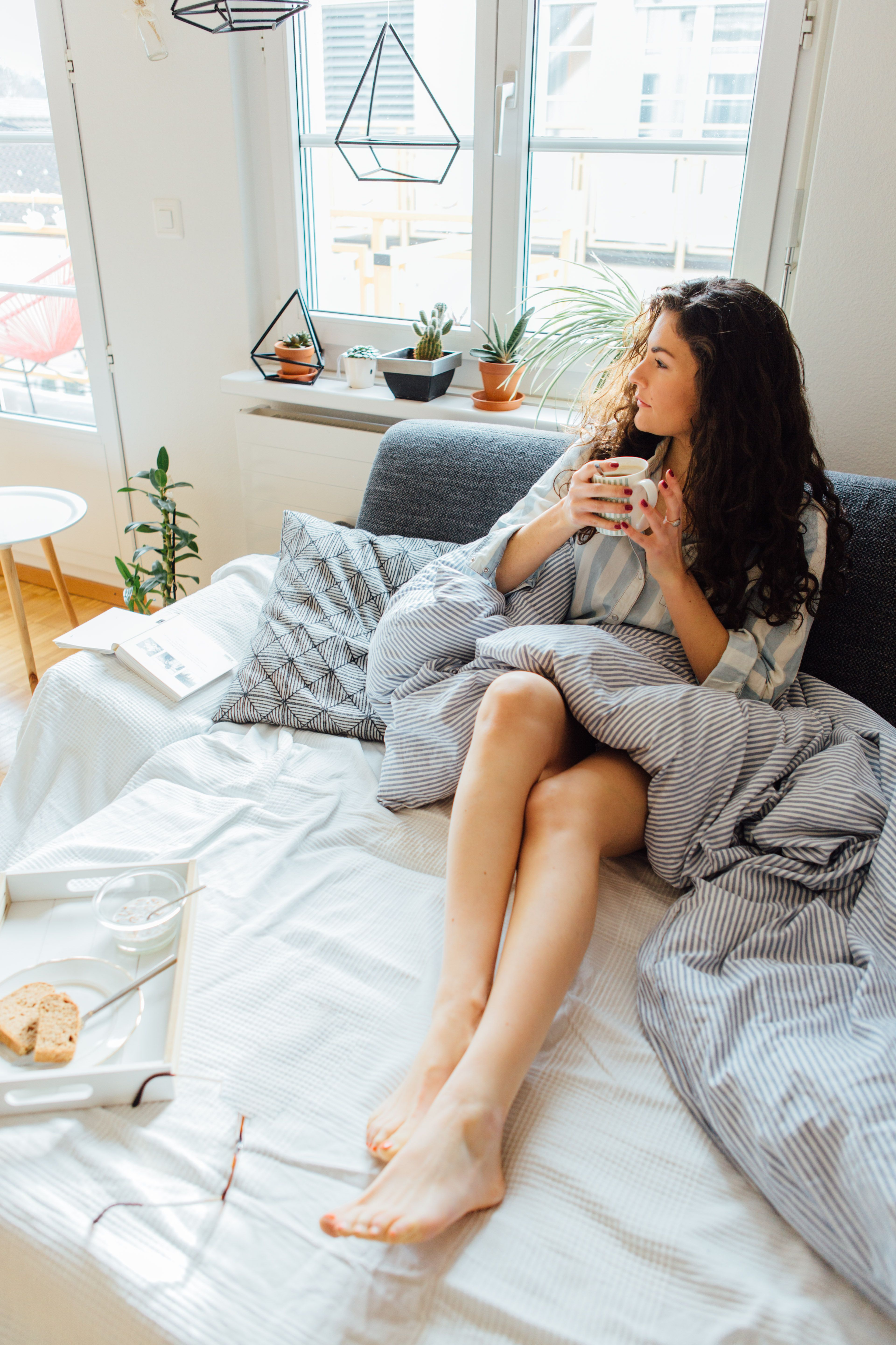 High Angle View Of Thoughtful Young Woman Looking Away While Having Coffee On Bed At Home