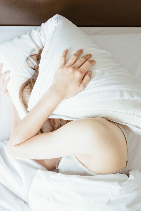High angle view of young woman lying on bed and she hate to waking up in the early morning.