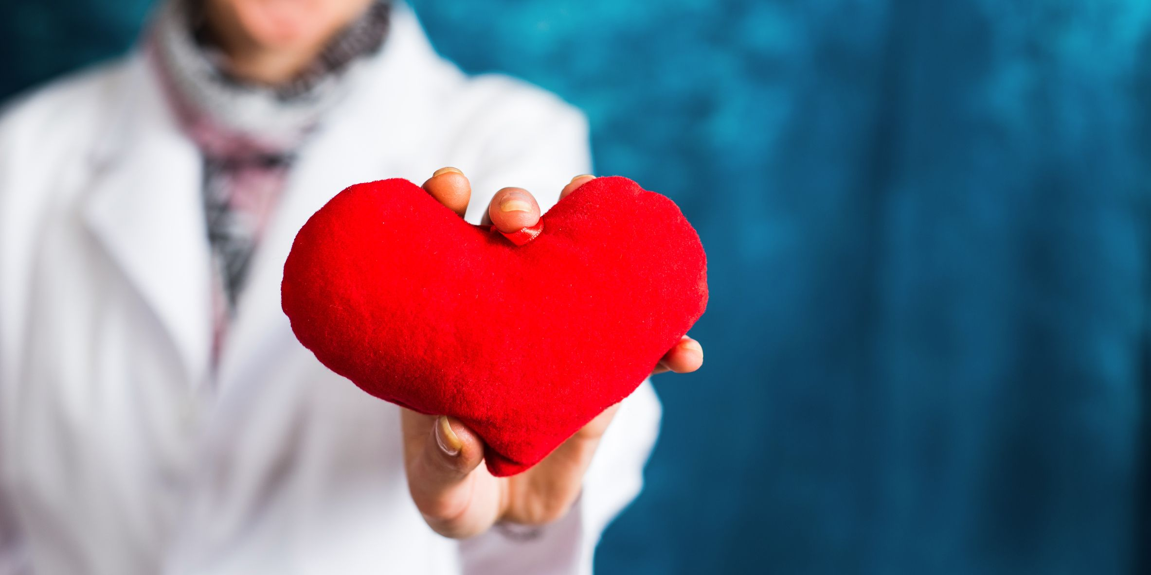 Female doctor holding a red heart closeup