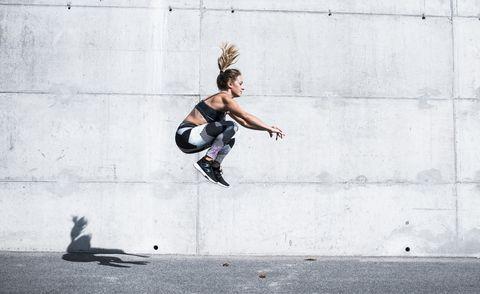 Mujer saltando con rodillas al pecho