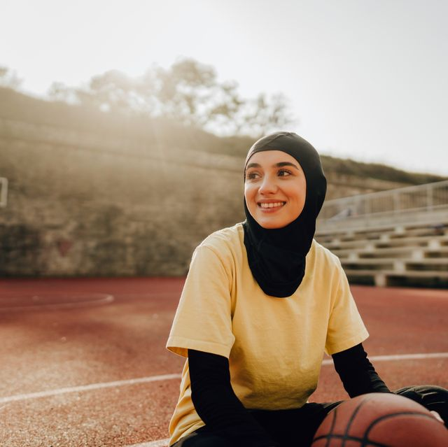 portrait of a smiling young woman with a hijab, ready to play some basketball