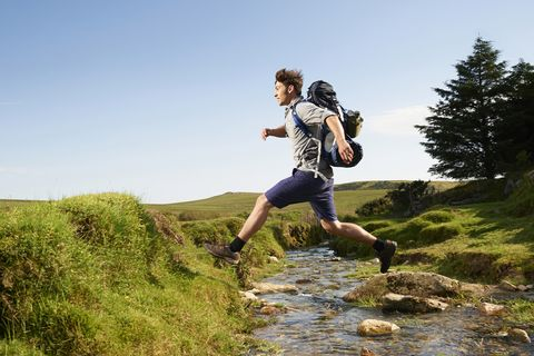 Hiker stepping over stream in countryside.