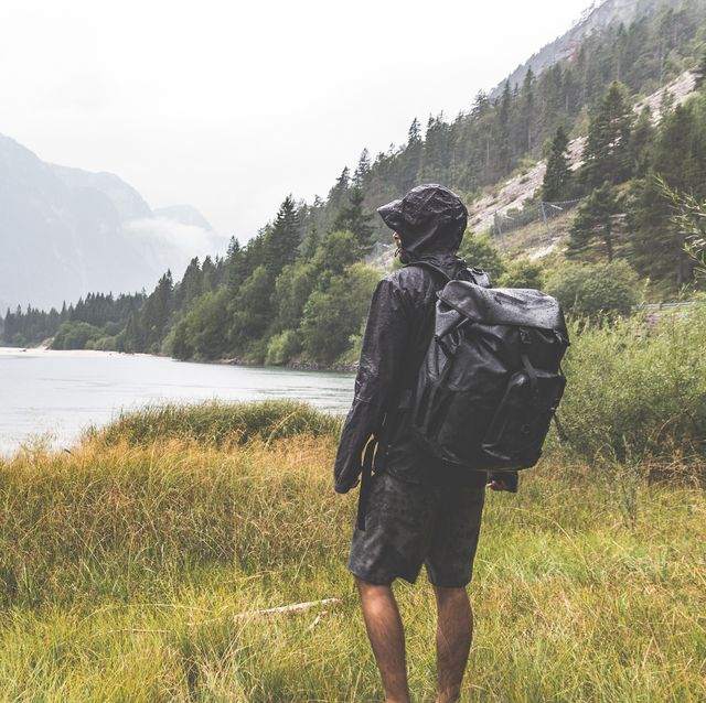 Hiker with a backpack watching the lake sourrounded by mountains