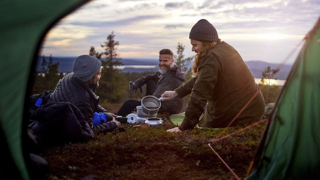 hikers preparing meal, chatting in front of tent, keimiotunturi, lapland, finland