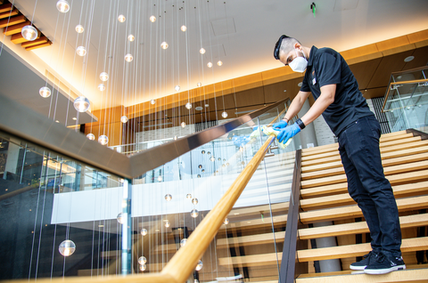 man cleaning stair railing inside a hilton hotel