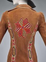 Burray Olson, woman's long coat, circa 1970, of Leather with Afghani beaded medallions, embroidered band appliques, and applied silver coins and brass beads.