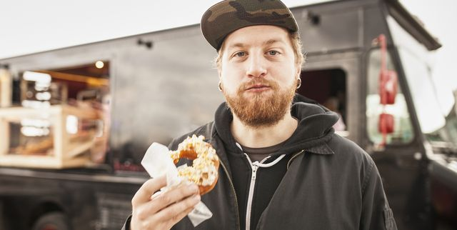 hipster man eating donut from food truck