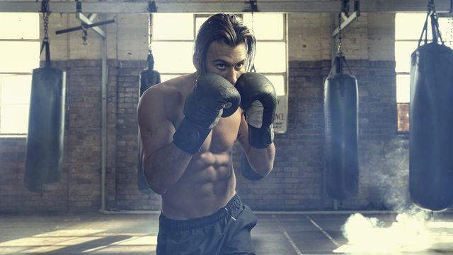 hispanic boxer posing in gymnasium
