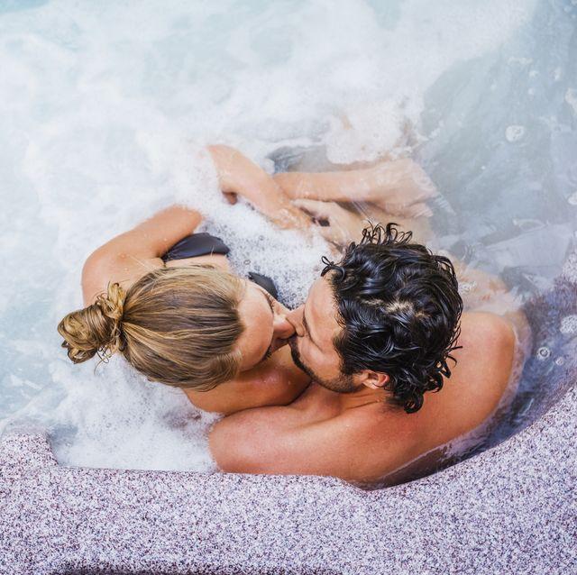 Hispanic couple kissing in hot tub