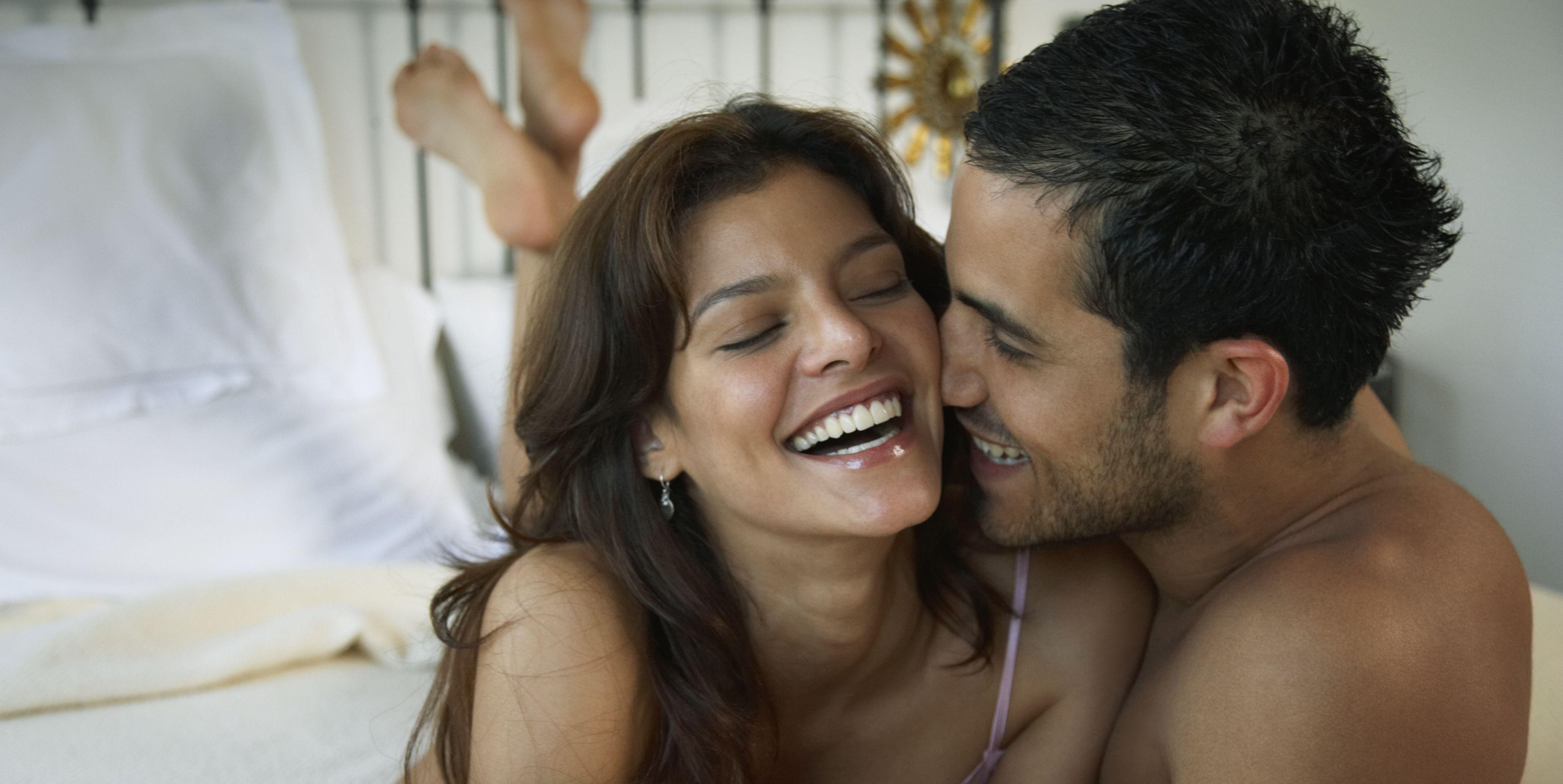 Hispanic couple laughing on bed