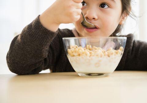hispanic girl eating bowl of cereal