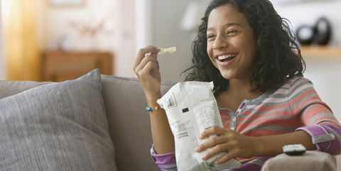 hispanic girl eating potato chips on sofa