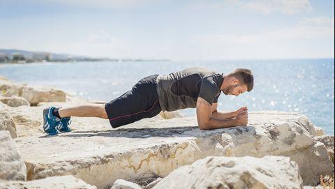Man in shirt en korte broek traint planking op rots aan zee