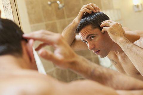 Hispanic man inspecting hair in bathroom mirror
