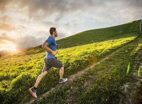 Hispanic man running on hill