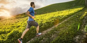 Hispanic man running on hill