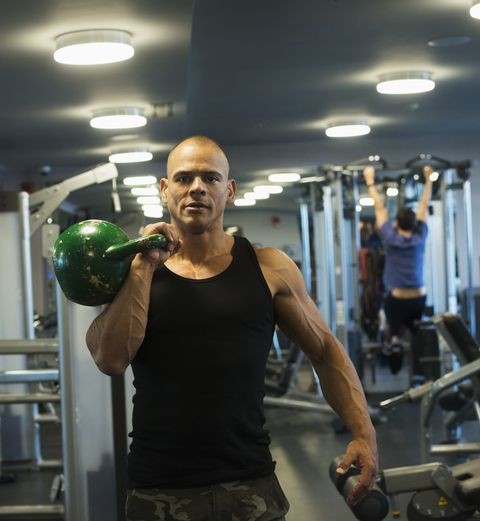 Hispanic man weightlifting with kettlebell in gymnasium