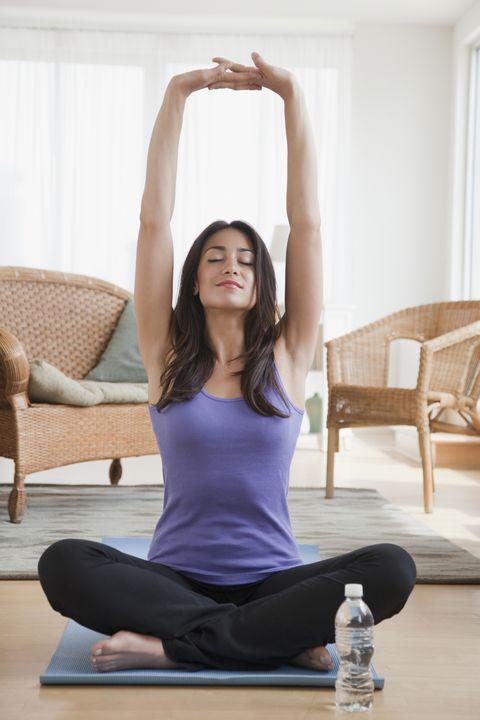 hispanic woman doing yoga in living room