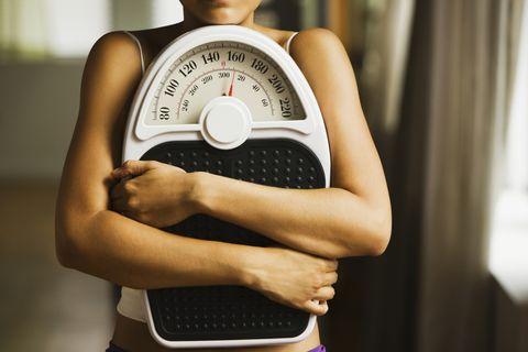 Hispanic woman holding bathroom scale